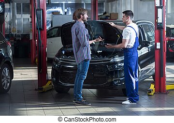 Automotive technician talking with client - Young automotive...