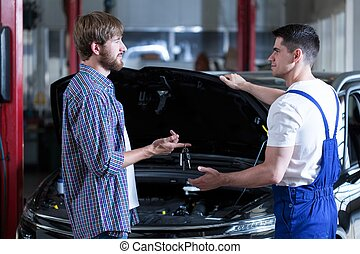 Man giving motor mechanic key to his car