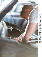Automobile mechanic repairing a car in service station