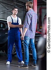 Auto mechanic and client - Satisfied auto mechanic and...