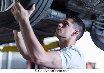 Automotive technician changing a wheel in the garage