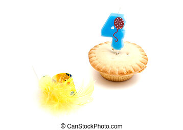 cupcake with four years birthday candle and whistle on white