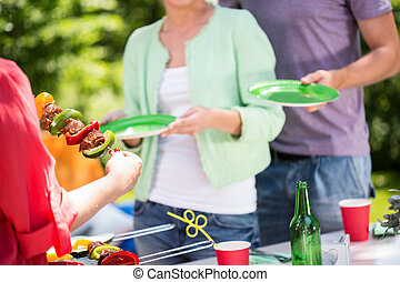 Female hands serving shashliks on barbecue party