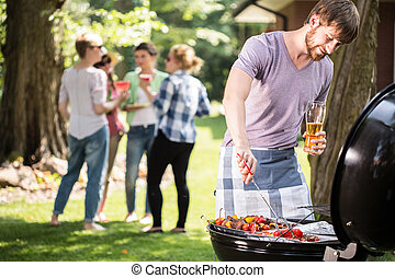 Young man doing barbecue and drinking beer