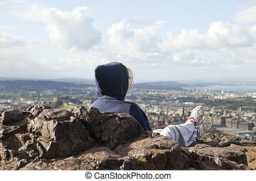Woman On Edinburgh Viewpoint - A woman sitting on top of...