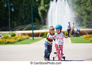 Boy and girl in park learning to ride a bike