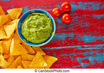 Mexican food nachos and guacamole in red grunge background