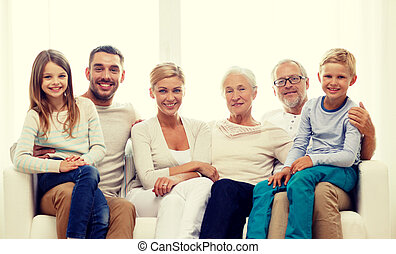 happy family sitting on couch at home - family, happiness,...