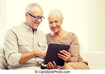 happy senior couple with tablet pc at home - family,...