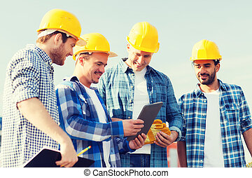 group of smiling builders with tablet pc outdoors -...