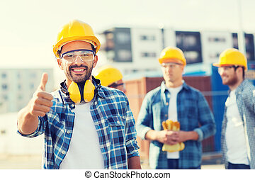 group of smiling builders in hardhats outdoors - business,...