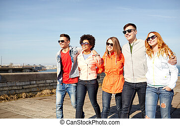 happy teenage friends walking along city street - tourism,...