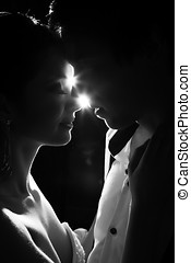 Married bride and groom dancing in a backlit scenario...