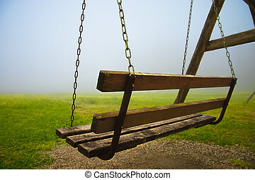 Bench in mist - abandoned wooden bench on chains in...