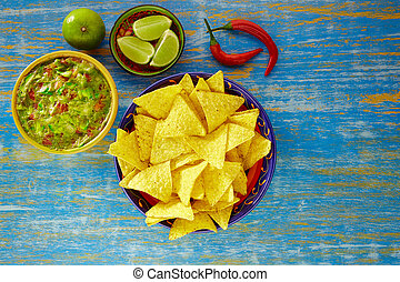 Mexican food nachos with guacamole chili peppers and  lemon