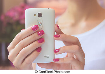 Mobile smart phone in female hands with a pink manicure on...