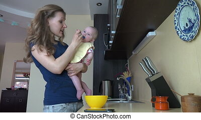 mother feed baby kitchen - Babysitter feed baby with spoon...