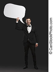 Holding a speach balloon - Handsome latino young man holding...
