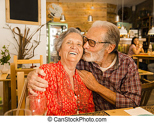 Old couple at the restaurant and having a good time