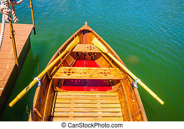 Wooden boat moored to a pier on the lake shore with rows