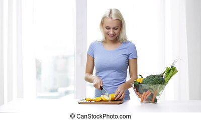 smiling young woman chopping squash at home - healthy...