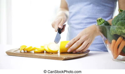 close up of young woman chopping squash at home - healthy...