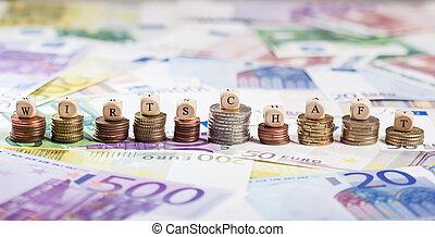 German word Wirtschaft on coin stacks, cash background -...