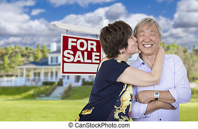 Affectionate Senior Chinese Couple In Front of House and Sign