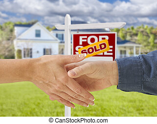 Shaking Hands in Front of New House and Sold Sign - Man and...