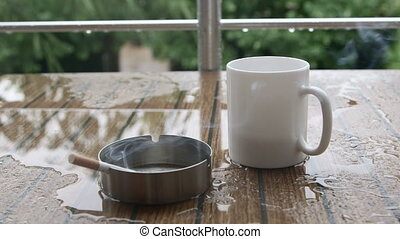 Cigarette in ashtray and cup of coffee on a table in rain...