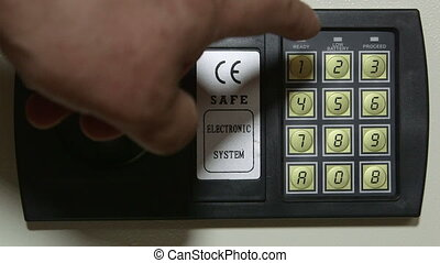 Entering code on a safe box at home or hotel - Male hand...