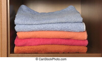 Female hands pulling out of the closet stack of colorful bath towels