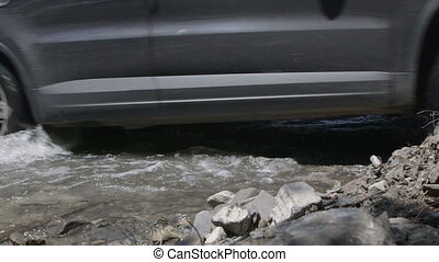 Car crossing mountain creek closeup