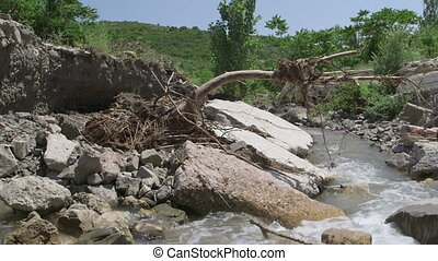 Concrete bridge over mountain river destroyed by flood waters