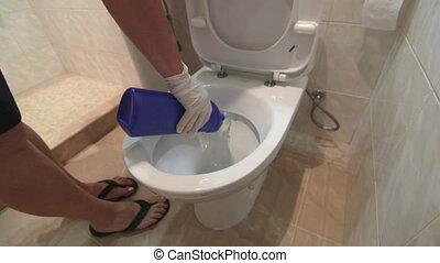 Woman cleaning toilet bowl in bathroom using liquid...