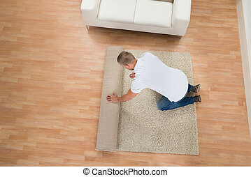 Young Man Unrolling Carpet