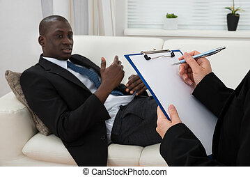 Patient On Couch And Psychiatrist Writing On Clipboard