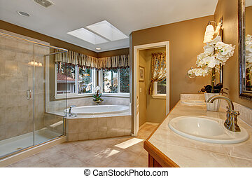 Large elegant master bathroom with tile floors, and glass shower.
