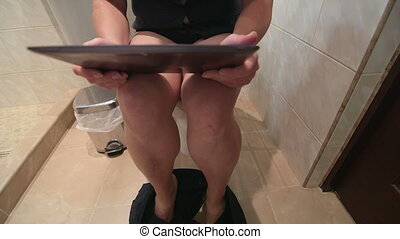 woman using digital tablet while sitting on toilet