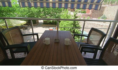 Terrace under folding awning in a sunny summer day - Table...