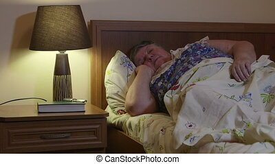 Obese senior woman talking on the phone lying on bed in...