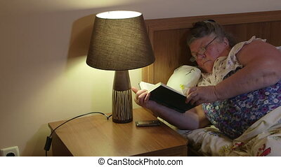 Obese old woman lying in bed at home reading book pan shot