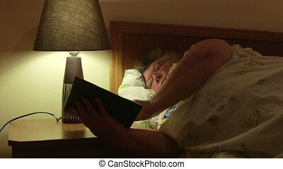 Obese old woman lying in bed at home reading book dolly shot