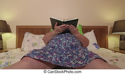 Overweight senior woman reading book lying in bed at home...