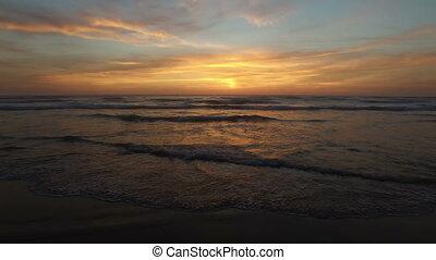 Aerial from ocean waves at sunset at the atlantic ocean
