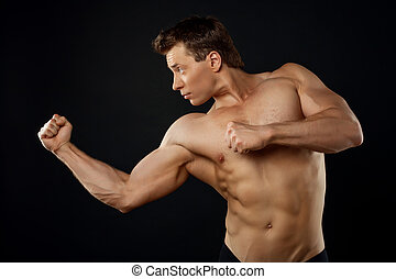 Attractive young sportsman is fighting with someone -...