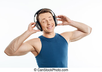 Beautiful young man is relaxing with earphones - Cheerful...