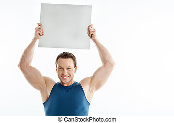 Handsome sportsman is presenting white sheet of paper -...