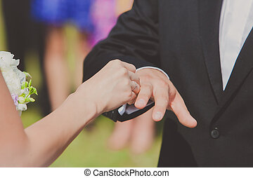 Bride is putting a ring on groom's finger