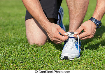 Fit young sportsman is tying his shoelaces - Close up of...